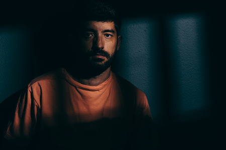 Prisoner man in dark cell illuminated only by a beam of light Stock Photo