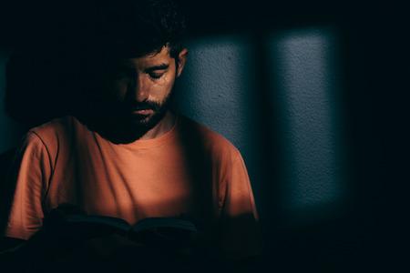 책 또는 성경을 읽고 어두운 세포에서 죄수 남자