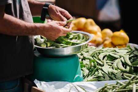Close up of the farmers market vendor shelling fava beans