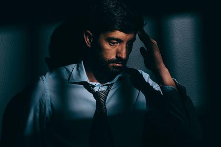 Businessman or political prisoner in dark cell. Concept of white collar crime