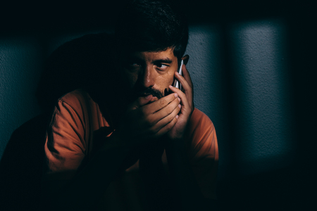 confined: Prisoner man in dark cell using cell phone discreetly Stock Photo