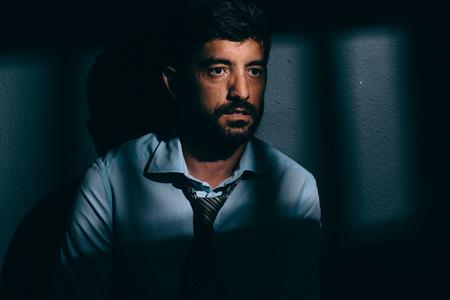 confined: Businessman or political prisoner in dark cell. Concept of white collar crime