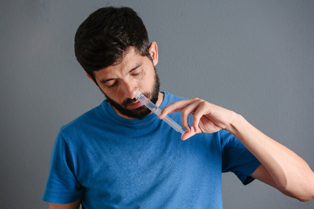 douche: Nasal wash. Man flushng his nose with syringe and saline isolated on gray background