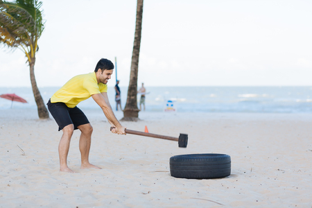Brazilian man working out functional training on the beach