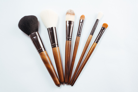 Makeup products and brushes on white background