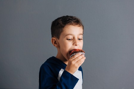 Brazilian child eating cupcake on gray background 스톡 콘텐츠