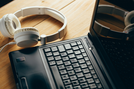 Headphones and laptop on wooden desk table. Music concept.