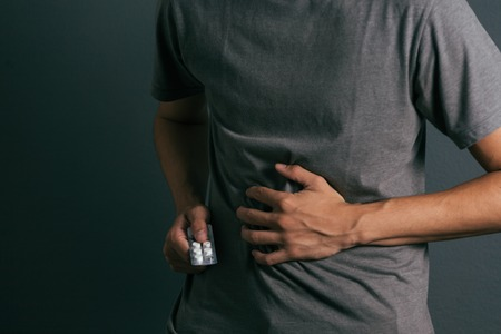 환약의 팩을 가진 젊은이는 복부 통증을 느낀다. 스톡 콘텐츠