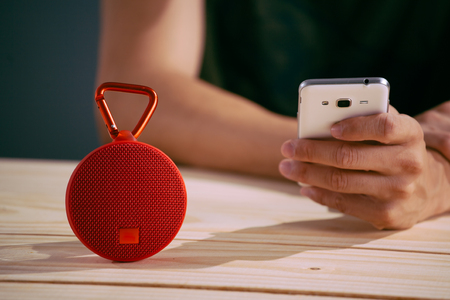 Man controlling smart speaker with smart phone