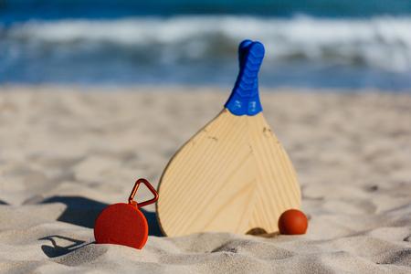 Wireless portable speaker and beach tennis rackets on the beach Stock Photo