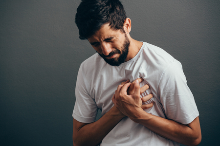 People, healthcare and problem concept - close up of man suffering from heart ache over gray background Stockfoto