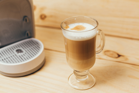 Espresso macchiato and coffee machine on wooden background Stock Photo