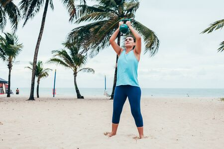 Cabedelo, Paraiba, Brazil - April 26, 2018 - Woman takes care of health and does exercises on the beach