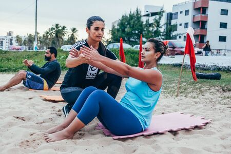 Cabedelo, Paraiba, Brazil - April 26, 2018 - Personal trainer supports clients on beach workout