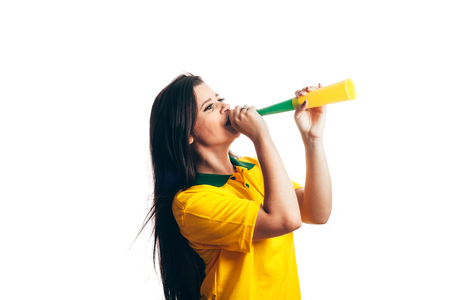 Brazilian fan cheering with a plastic horn isolated on white background