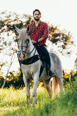 Young man riding white horse on the countryside Stock Photo