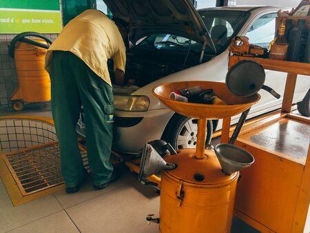 Cabedelo, Paraiba, Brazil - July 5, 2018 - Auto mechanic technician replaces motor oil into automobile engine at maintenance repair service station Sajtókép