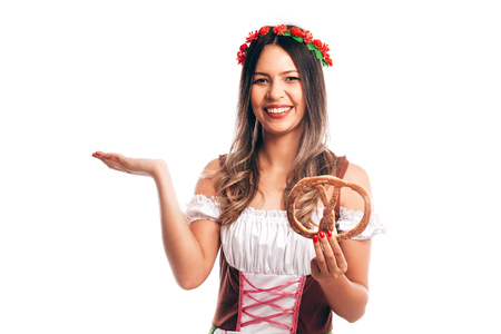 Attractive girl in traditional german costume with pretzel on Oktoberfest, isolated on white
