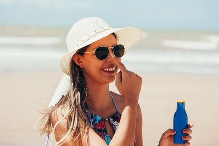 Sunscreen, sunblock. Woman putting solar cream on nose smiling beautiful summer day. Skincare. Girl applying sun cream