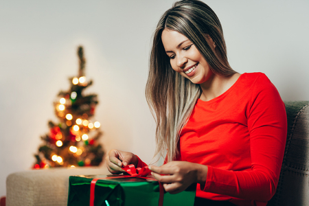 Young woman opening Christmas gift, sitting in the living room Stock Photo