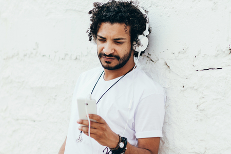 Closeup portrait of young handsome man listening to music on headphones Imagens