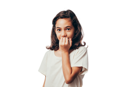 Portrait of young girl biting her nails on white background Foto de archivo