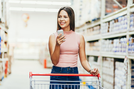 Woman using mobile phone while shopping in supermarket Foto de archivo