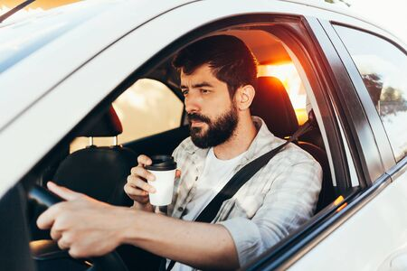 Man drinking coffee while driving his car 写真素材