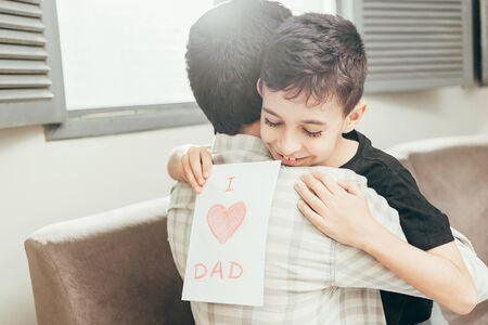 Happy fathers day! Son congratulating dad and giving him a greeting card. Daddy and son smiling and hugging. Family holiday and togetherness.