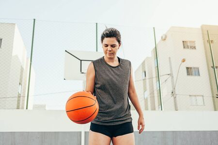 Young female basketball player training outdoors on a local court Reklamní fotografie