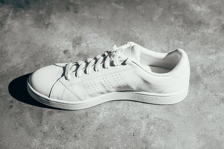 White sneaker on gray background. Stylish white sneaker