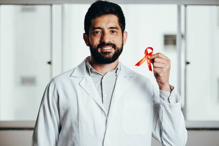 Red ribbon for HIV illness awareness in doctors hand, 1 December World AIDS Day concept.