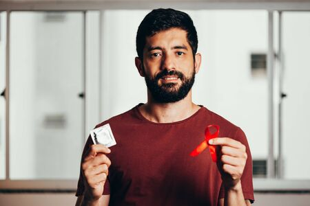 Man holding condom and red ribbon for HIV illness awareness, 1 December World AIDS Day concept.