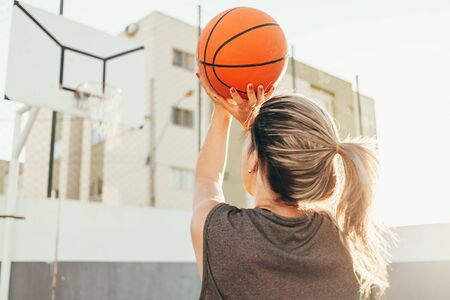 Young female basketball player training outdoors on a local court 版權商用圖片