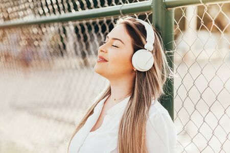 Beautiful plus-size woman listening to music in the park 版權商用圖片
