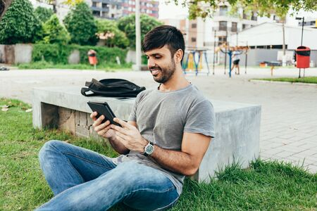 Young man reading e-book in the park