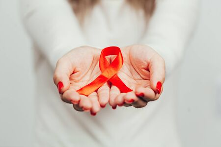 Woman holding red ribbon for HIV illness awareness, 1 December World AIDS Day concept.