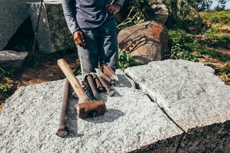 Granite extraction for paving cobblestones. Worker and his tools.