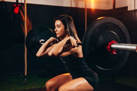 Muscular woman in gym doing heavy weight exercises. Young woman doing weight lifting at health club Zdjęcie Seryjne