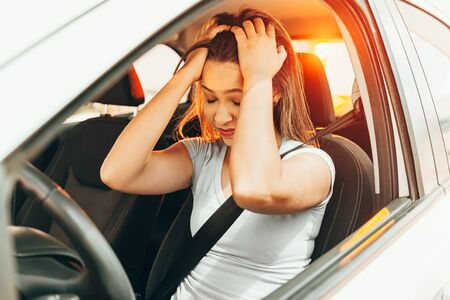 Stressed young woman driver sitting inside her car Banco de Imagens