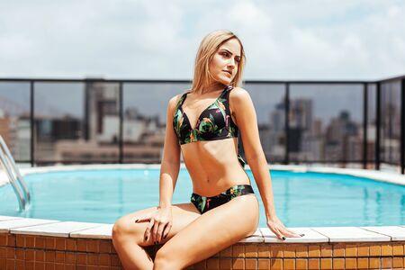 Young woman wearing bikini tanning in pool on rooftop building Archivio Fotografico - 134849308