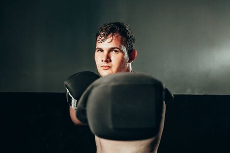 Portrait of male boxer punching in the gym