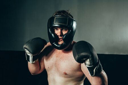 Portrait of male boxer wearing gloves and helmet at gym