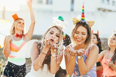 Brazilian Carnival. Young women in costume enjoying the carnival party blowing confetti Archivio Fotografico - 140758404