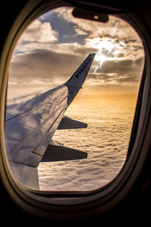 DUBLIN, IRELAND - APRIL 23, 2017- Ryanair logo in the wing of the airplane with the sky as the background. Ryanair has cheap flights in Europe 에디토리얼