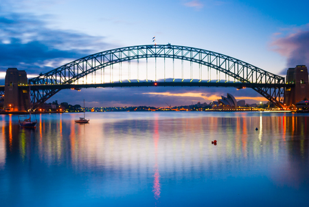 Harbour harbor bridge across ocean sea water to city centre center downtown under blue sky during sunset sunrise 写真素材