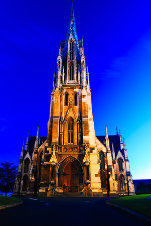 Old stone cathedral church in the downtown city center during calm peaceful sunset Stock Photo