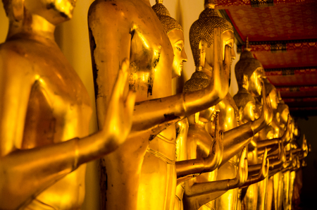 Yellow gold standing Buddha meditating in the old ancient temple in South East Asia Stock Photo
