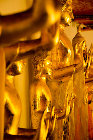 Gold yellow statue of standing Buddha meditating and praying in a sacred temple complex in East Asia