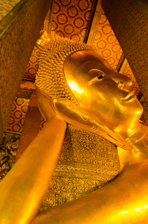 Gold yellow statue of sleeping Buddha in a sacred temple complex in East Asia 免版税图像